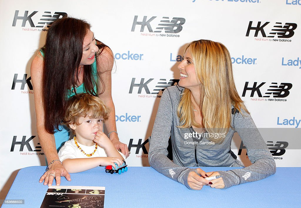 Heidi Klum (R) signs autographs for fans at the launch of her new Heidi Klum for New Balance Collection at Lady Foot Locker on March 14, 2013 in Culver City, California.
