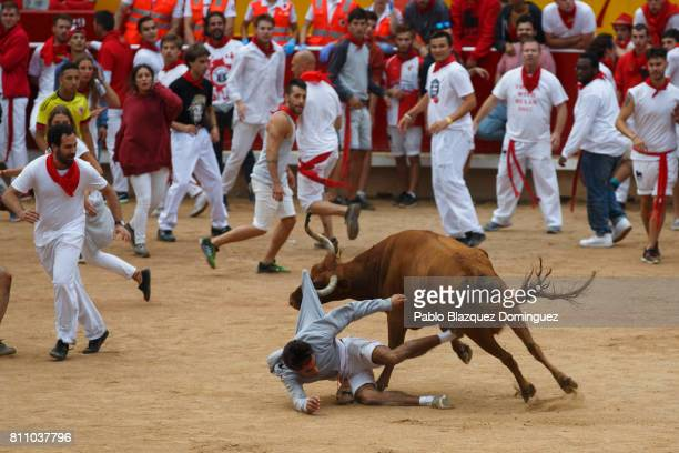 A heifer pulls lift a reveller in the bullring during the fourth day of the San Fermin Running of the Bulls festival on July 9 2017 in Pamplona Spain...