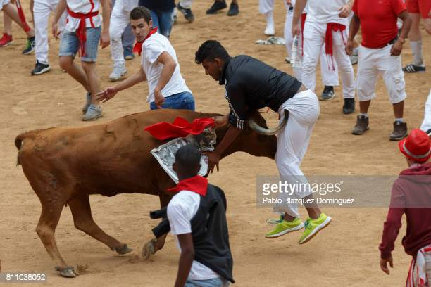 A heifer tosses a reveller in the bullring during the fourth day of the San Fermin Running of the Bulls festival on July 9 2017 in Pamplona Spain The...
