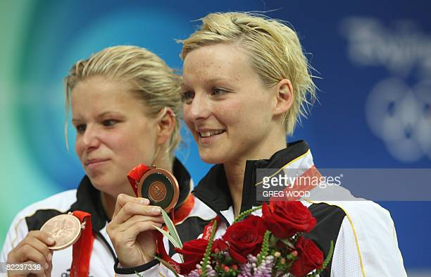 Heike Fischer and Ditte Kotzian of Germany hold their medals on the podium after the women's synchronised 3m springboard diving competition final at...