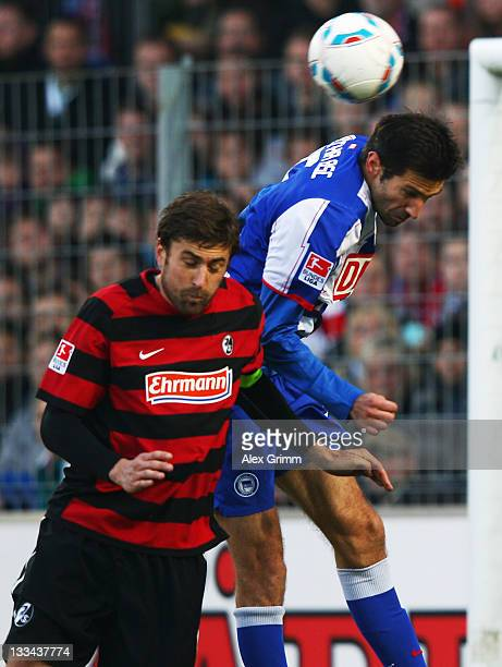 Heiko Butscher of Freiburg jumps for a header with Andre Mijatovic of Berlin during the Bundesliga match between SC Freiburg and Hertha BSC Berlin at...