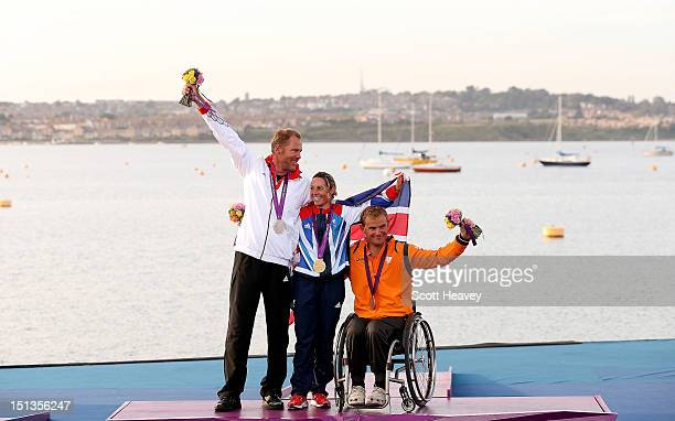 Heiko Kroger of Germany celebrates with Helena Lucas of Great Britain and Thierry Schmitter of Netherlands in the single person keelboat on day 8 of...