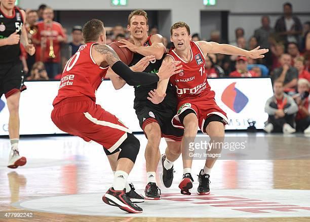 Heiko Schaffartzik of FC Bayern Muenchen under pressure from Daniel Theis of Brose Baskets Bamberg and Janis Strelnieks of Brose Baskets Bamberg...