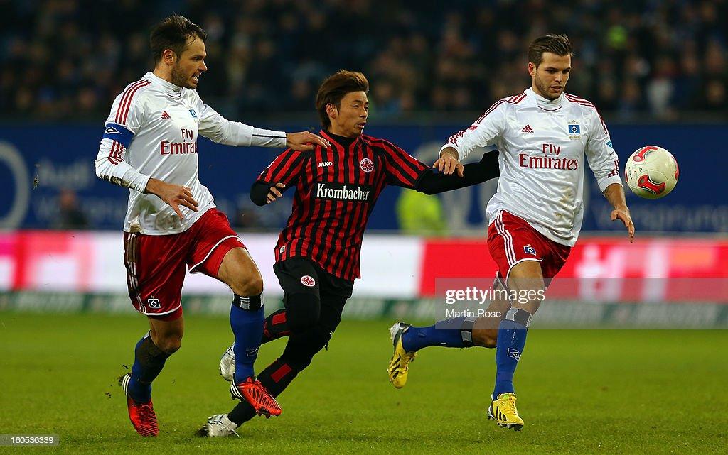 Heiko Westermann and Dennis Diekmeier of Hamburg and Takashi Inui of Frankfurt battle for the ball during the Bundesliga match between Hamburger SV...