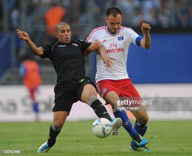 Heiko Westermann of Hamburg is challenged by Sofiane Feghouli of Valencia during the preseason friendly match between Hamburger SV and Valencia at...
