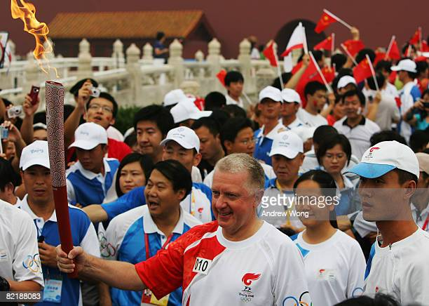 Hein Verbruggen chairman of the International Olympic Committee Coordination Commission carries the Olympic torch on Tiananmen Square during the...