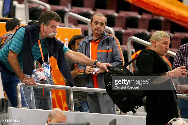 Heiner Brand pulls handball expert Stefan kretzschmar at his bagpack prior to the IHF Men's Handball World Championship group D match between Germany...