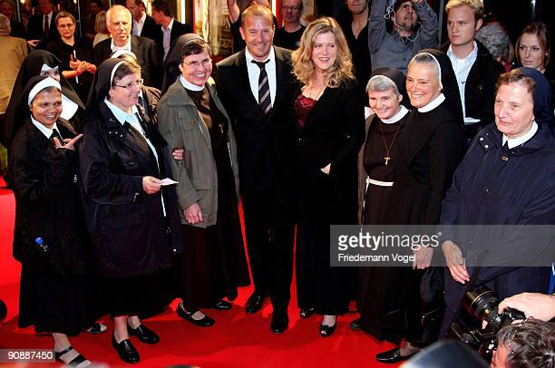 Heino Ferch and Barbara Sukowa pose on the red carpet with nuns as they arrive for the premiere of the film 'Vision From The Life Of Hildegard Von...