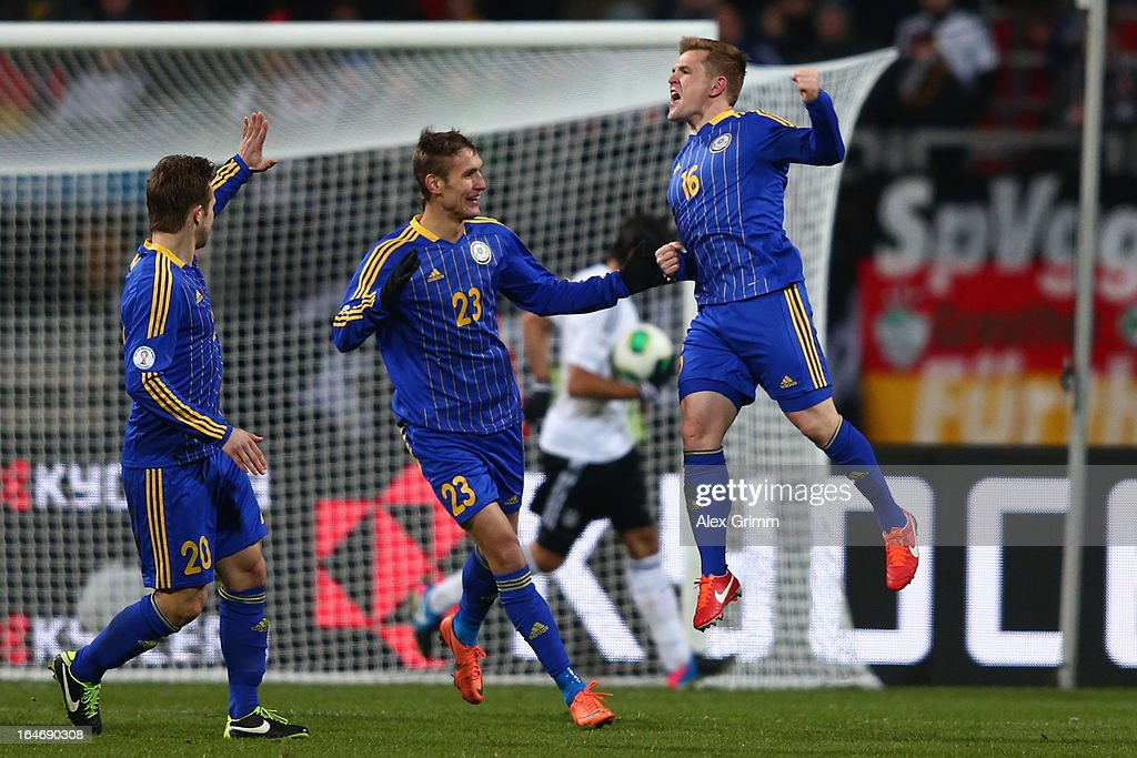 Heinrich Schmidtgal of Kazakhstan celebrates his team's first goal with team mates Valery Korobkin and Konstantin Engel (R-L) during the FIFA 2014 World Cup qualifier between Germany and Kazakhstan at Grundig-Stadion on March 26, 2013 in Nuremberg, Germany.