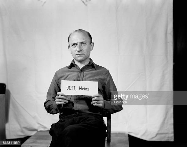 Heinz Jost Brigadier General in the SS and a member of the SD holds his name up on a card He is on trial in Nurnburg accused of taking part in the...