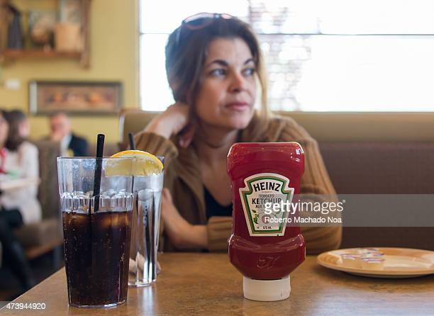 RESTAURANT TORONTO ONTARIO CANADA Heinz Ketchup over a table in restaurant while an hispanic woman is waiting for her food to be served