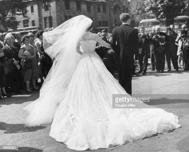 Heiress Patricia Cottingham daughter of racehorse owner Vera Lilley and Patrick Oswald face the cameras after their wedding ceremony at St Margaret's...