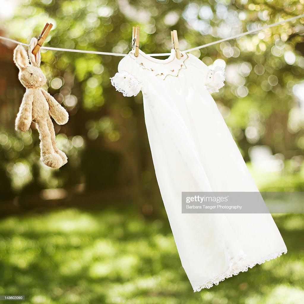 Heirloom smocked baby dress and stuffed bunny hang : Stock Photo