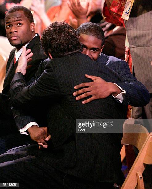 Heisman candidate quarterback Vince Young of the Texas Longhorns looks on as running back Reggie Bush of the USC Trojans embraces teammate and fellow...