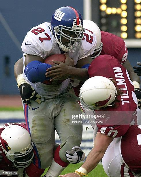 Heisman Trophy winner Ron Dayne of the New York Giants attracts a number of the Arizona Cardinals including Pat Tillman and Corey Smith while gaining...
