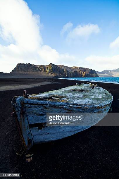 Antique timber whaling boat ruins stranded in black volcanic sand.