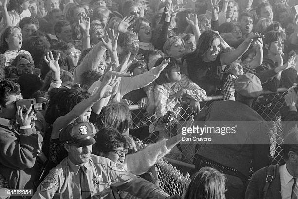 Held back by police officers fans scream and wave their greetings as British pop group the Beatles arrive at the airport for a US tour Los Angeles...