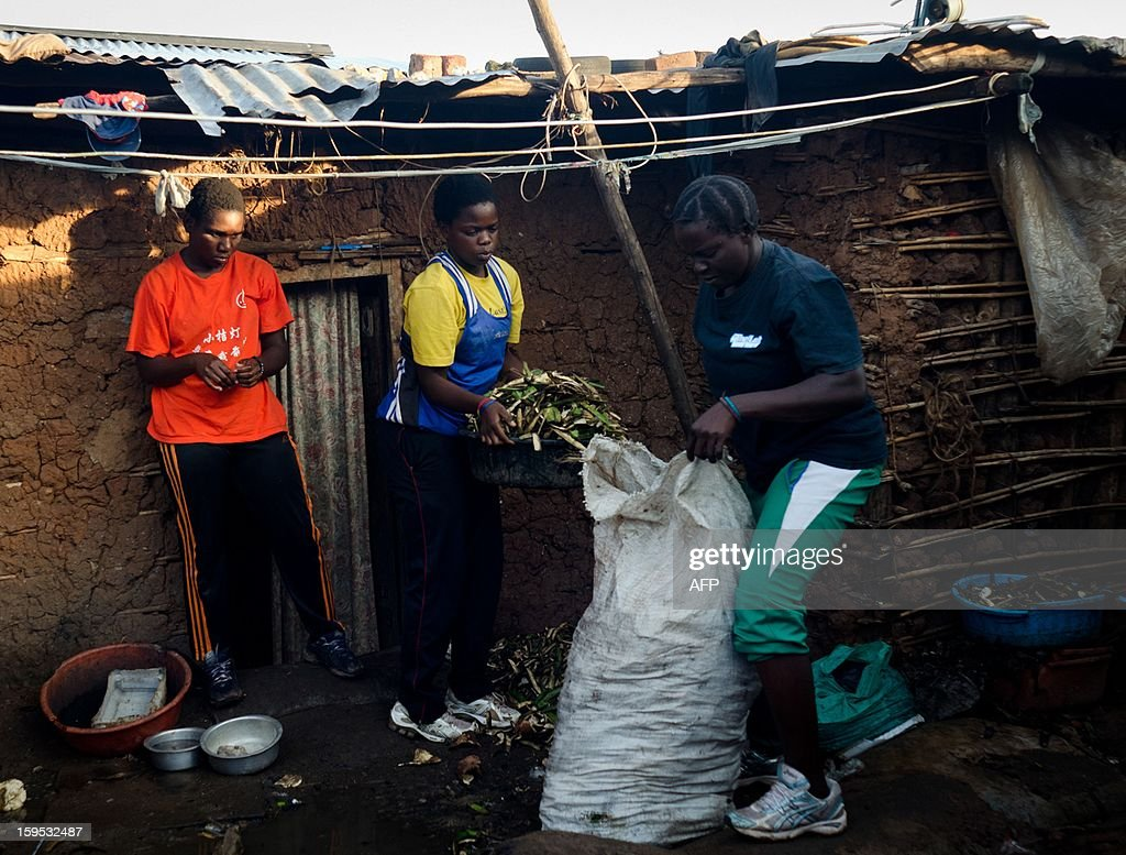 Helen (R) and Diana Turyanabo (C) collect banana peelings in a slum in the Ugandan capital Kampala on December 18, 2012. Helen, 23, along with her younger sister Diana, 20, living in a trash ridden slum area, are two young women who stand out amongst their neighbours as they both are professional boxers, literally trying to fight their way out of poverty. After a man tried to rape Helen, the older of the two sisters, it inspired her to learn how to fight inorder defend herself, and despite recently winning a medal in an East African Regional Championship, Helen and Diana still have to collect garbage to sell to get money for food for themselves and nearly 20 other people, cramped into two rooms with no water or electricity. AFP PHOTO/Michele Sibiloni.