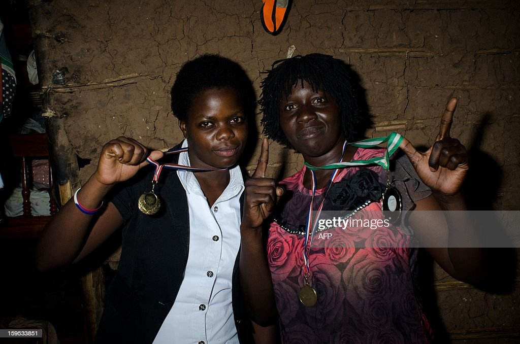 Helen (R) and Diana Turyanabo pose with medals that Helen has won on December 14, 2012 at the Kataanga slum in the Ugandan capital, Kampala. Helen, 23, along with her younger sister Diana, 20, living in a trash ridden slum area, are two young women who stand out amongst their neighbours as they both are professional boxers, literally trying to fight their way out of poverty. After a man tried to rape Helen, the older of the two sisters, it inspired her to learn how to fight inorder defend herself, and despite recently winning a medal in an East African Regional Championship, Helen and Diana still have to collect garbage to sell to get money for food for themselves and nearly 20 other people, cramped into two rooms with no water or electricity. AFP PHOTO/Michele Sibiloni.