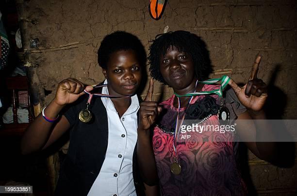 Helen and Diana Turyanabo pose with medals that Helen has won on December 14 2012 at the Kataanga slum in the Ugandan capital Kampala Helen along...