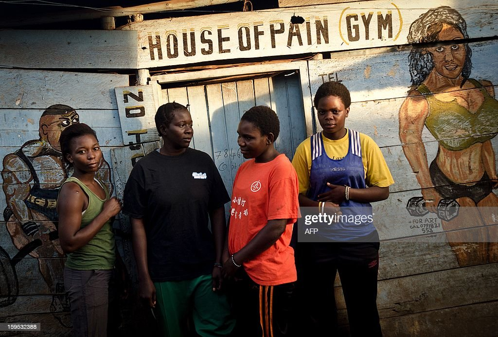 Helen (2nd R) and Diana Turyanabo (R) stand along with a couple of training mates outside the boxing gym at a slum in the Ugandan capital Kampala on December 18, 2012. Helen, 23, along with her younger sister Diana, 20, living in a trash ridden slum area, are two young women who stand out amongst their neighbours as they both are professional boxers, literally trying to fight their way out of poverty. After a man tried to rape Helen, the older of the two sisters, it inspired her to learn how to fight inorder defend herself, and despite recently winning a medal in an East African Regional Championship, Helen and Diana still have to collect garbage to sell to get money for food for themselves and nearly 20 other people, cramped into two rooms with no water or electricity. AFP PHOTO/Michele Sibiloni.