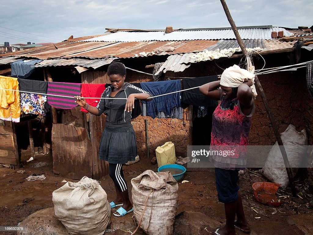 Helen (R) and Diana Turyanabo (L) stand outside their shantee home at Kataanga slum in the Ugandan capital, Kampala, on December 18, 2012. Helen, 23, along with her younger sister Diana, 20, living in a trash ridden slum area, are two young women who stand out amongst their neighbours as they both are professional boxers, literally trying to fight their way out of poverty. After a man tried to rape Helen, the older of the two sisters, it inspired her to learn how to fight inorder defend herself, and despite recently winning a medal in an East African Regional Championship, Helen and Diana still have to collect garbage to sell to get money for food for themselves and nearly 20 other people, cramped into two rooms with no water or electricity. AFP PHOTO/Michele Sibiloni.