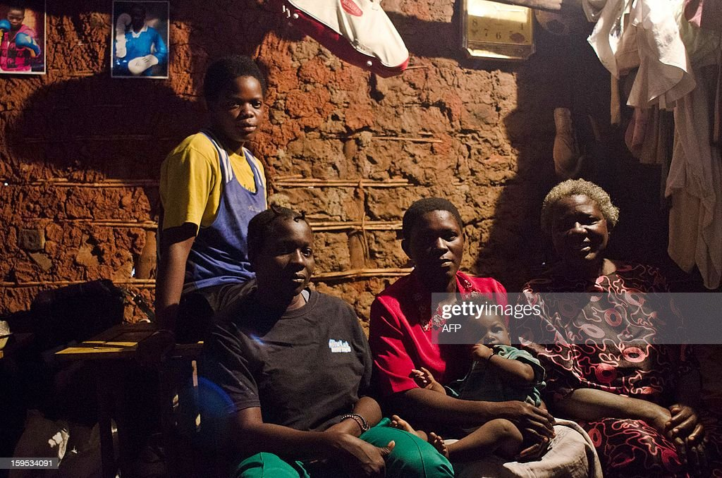 Helen (2nd L) and Diana Tutyanabo (L) with with their mother (R) and another unidentified relative pose at their home in the Kataanga slum of the Ugandan capital Kampala on December 4, 2012. Helen, 23, along with her younger sister Diana, 20, living in a trash ridden slum area, are two young women who stand out amongst their neighbours as they both are professional boxers, literally trying to fight their way out of poverty. After a man tried to rape Helen, the older of the two sisters, it inspired her to learn how to fight inorder defend herself, and despite recently winning a medal in an East African Regional Championship, Helen and Diana still have to collect garbage to sell to get money for food for themselves and nearly 20 other people, cramped into two rooms with no water or electricity. AFP PHOTO/Michele Sibiloni.