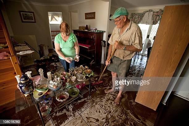 Helen and Trevor Goschnick mop up the aftermath of a metre of flood waters that flowed through their Fernvale home near Ipswich some 40 kms southwest...