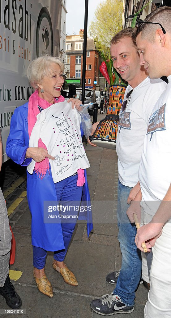 Helen Mirren presents her T shirt to the 'As One In The Park' festival team as they present her with flowers and a drum as an apology for the disruption to her stage performance on May 7, 2013 in London, England.