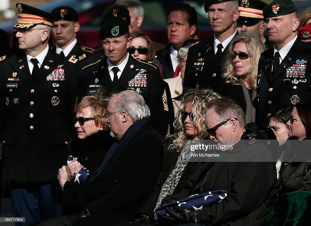 Helen Pedersen-Keiser (L) clutches the American flag that covered her son's casket during a burial service for U.S. Army Capt. Andrew Pedersen-Keel at Arlington National Cemetery March 27, 2013 in Arlington, Virginia. Capt. Pedersen-Keel was killed on March 11, 2013 while serving in Wardak Province, Afghanistan from injuries sustained when attacked by small arms fire from a man in an Afghan police uniform, according to reports.