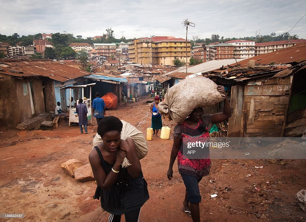 Helen [R] and Diana Turyanabo [L] carry sacks of banana peelings from Kataanga slum on December 18, 2012 on their way to sell the peelings on a roadside in the Ugandan capital, Kampala. Helen, 23, along with her younger sister Diana, 20, living in a trash ridden slum area, are two young women who stand out amongst their neighbours as they both are professional boxers, literally trying to fight their way out of poverty. After a man tried to rape Helen, the older of the two sisters, it inspired her to learn how to fight inorder defend herself, and despite recently winning a medal in an East African Regional Championship, Helen and Diana still have to collect garbage to sell to get money for food for themselves and nearly 20 other people, cramped into two rooms with no water or electricity. AFP PHOTO/Michele Sibiloni.