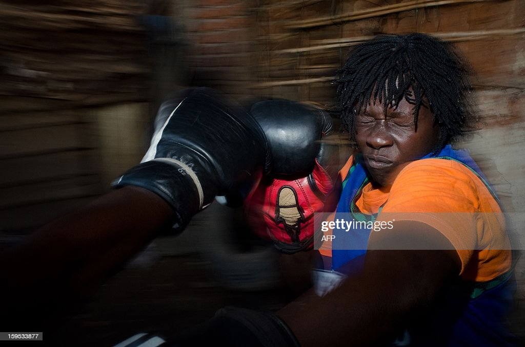 Helen Turyanabo, 23, is seen during a boxing training session at a gym in a slum of the Ugandan capital, Kampala on December 12, 2012. Helen, 23, along with her younger sister Diana, 20, living in a trash ridden slum area, are two young women who stand out amongst their neighbours as they both are professional boxers, literally trying to fight their way out of poverty. After a man tried to rape Helen, the older of the two sisters, it inspired her to learn how to fight inorder defend herself, and despite recently winning a medal in an East African Regional Championship, Helen and Diana still have to collect garbage to sell to get money for food for themselves and nearly 20 other people, cramped into two rooms with no water or electricity. AFP PHOTO/Michele Sibiloni.
