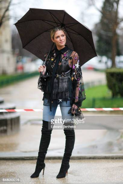 Helena Bordon wears a mesh top with colored printed stars a tie a sleeveless black leather jacket with fringes blue denim jeans pants black thigh...