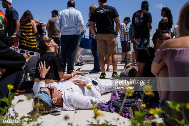 Helena Perez and Gustavo Carvajal take a look of the solar eclipse at the Phillip and Patricia Frost Museum of Science on Monday Aug 21 2017