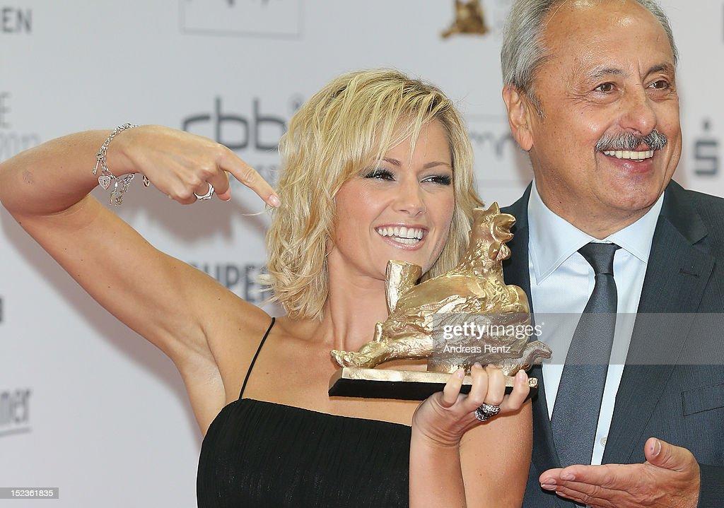 Helene Fischer holds up her award while Wolfgang Stumph smiles at 'Goldene Henne' 2012 award on September 19, 2012 in Berlin, Germany.