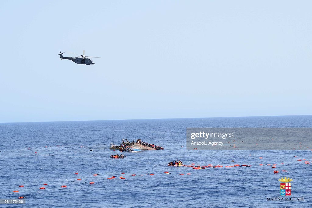 A helicopter approaches to the capsized boat as Italian marines rescue migrants from an overcrowded boat at Sicilian Strait, between Libya and Italy, in Mediterranean sea on May 25, 2016. The Italian Navy saved around 500 migrants as they found dead bodies of seven migrants in the sea during the operations.