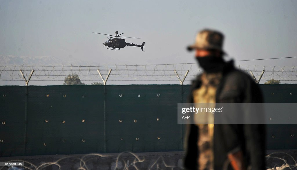 A helicopter belonging to NATO-led International Security Assistance Force (ISAF) flies over a base near the site of a suicide attack in Jalalabad on December 2, 2012. Taliban insurgents launched a major suicide attack Sunday against a NATO base at an Afghan city airport, killing three Afghan guards and wounding several foreign troops, officials said. NATO helicopters fired on the insurgents as they followed up a car bombing at the perimeter gate of the Jalalabad airport with rocket-propelled grenades, mortars and small arms fire. AFP PHOTO/ Noorullah Shirzada