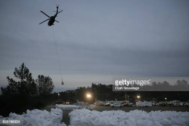 A helicopter carries a bag of rocks tfrom an emergeny staging area near the Oroville Dam on February 13 2017 in Oroville California Almost 200000...