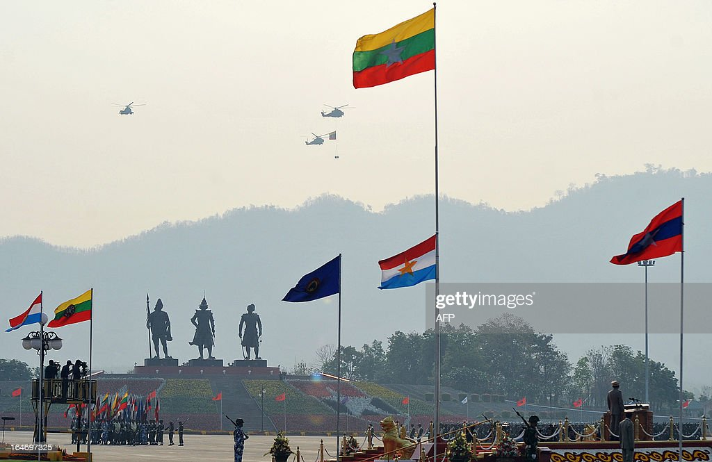 A helicopter (top) carries a national flag over a parade ground during a ceremony marking Myanmar's 68th Armed Forces Day in Naypyidaw on March 27, 2013. Opposition leader Aung San Suu Kyi attended Myanmar's Armed Forces Day for the first time. AFP PHOTO / Ye Aung THU