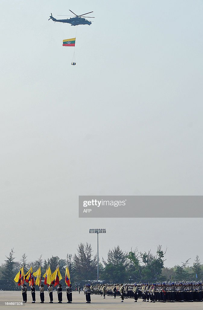 A helicopter carries a national flag over a parade ground during a ceremony marking Myanmar's 68th Armed Forces Day in Naypyidaw on March 27, 2013. Opposition leader Aung San Suu Kyi attended Myanmar's Armed Forces Day for the first time. AFP PHOTO / Ye Aung THU