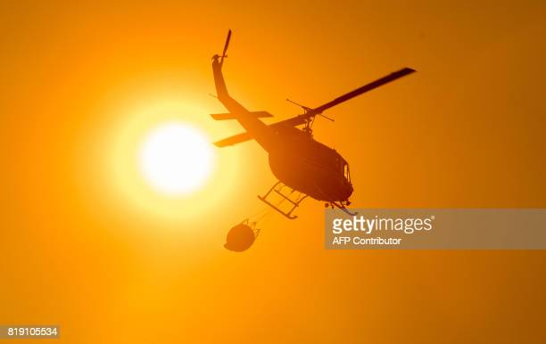 A helicopter carries water to a drop point over the Detwiler fire in Mariposa California on July 19 2017 The Detwiler fire is currently at 7 percent...