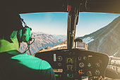 Helicopter cockpit interior with rear view of unrecognizable men co-pilot, flying high up altitude over Mont Blanc massif in French Alps mountains at sunset. The men is unrecognizable and looking thro