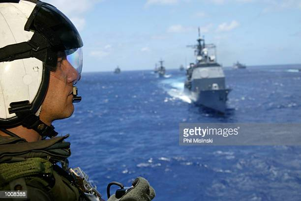 UH3H helicopter crew chief Randall Elkins observes naval ships from multiple nations steam in formation during the RIMPAC excercise operations July...