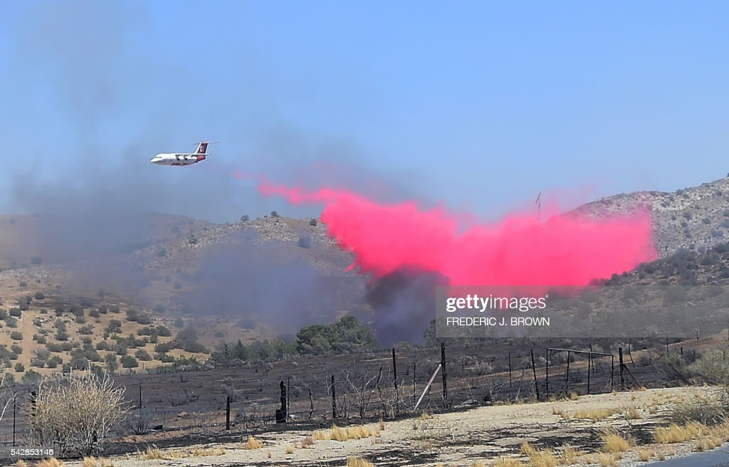 A helicopter drops retardant over a fire in the mountains around Lake Isabella, California on June 24, 2016. An intense wildfire broke out yesterday afternoon scorched dozens of homes and structures in this mountainous community northeast of Bakersfield in Kern County. / AFP / FREDERIC