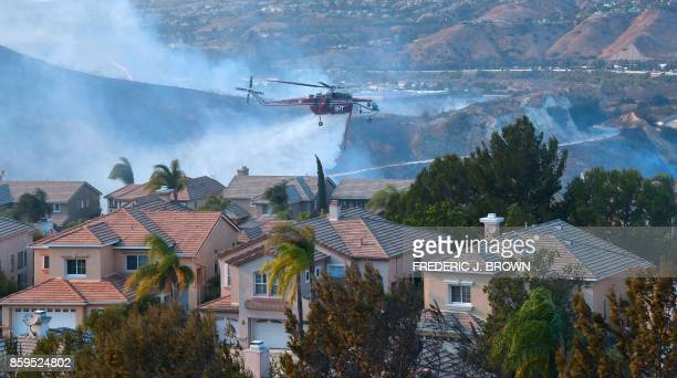 TOPSHOT A helicopter drops water near homes at the Anaheim Hills neighborhood in Anaheim California on October 9 after a fire spread quickly through...