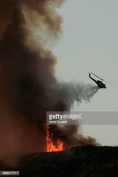 A helicopter drops water on a small brush fire broke out along the 101 freeway in Newbury Park on tuesday afternoon December 9 2008 A red flag...