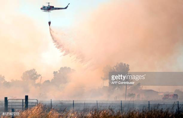 TOPSHOT A helicopter drops water on an 80 acre spot fire that broke out in Butte County California on July 10 2017 More than a dozen wildfires were...