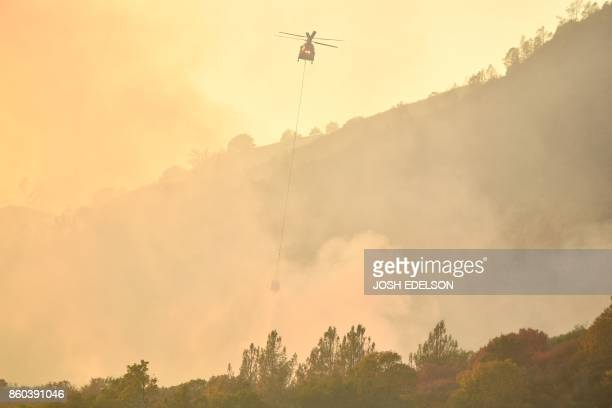 TOPSHOT A helicopter drops water on flames in Calistoga California on October 11 2017 Multiple winddriven fires continue to ravage the area and have...