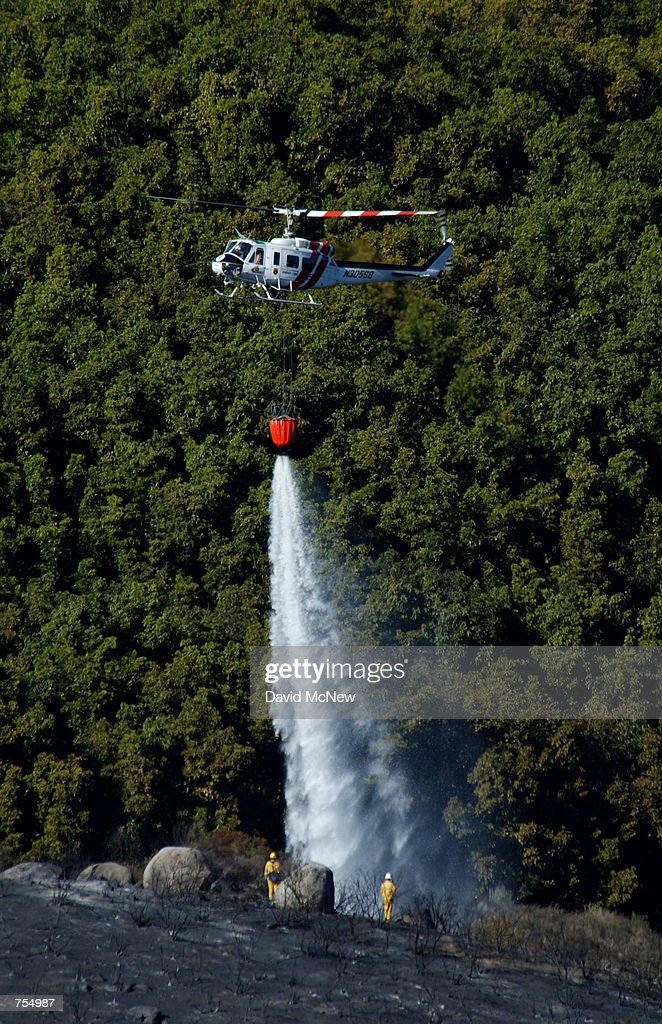 A helicopter drops water on scorched ground near an avocado grove after a wildfire destroyed 35 to 40 homes the previous evening February 11 2002 in...
