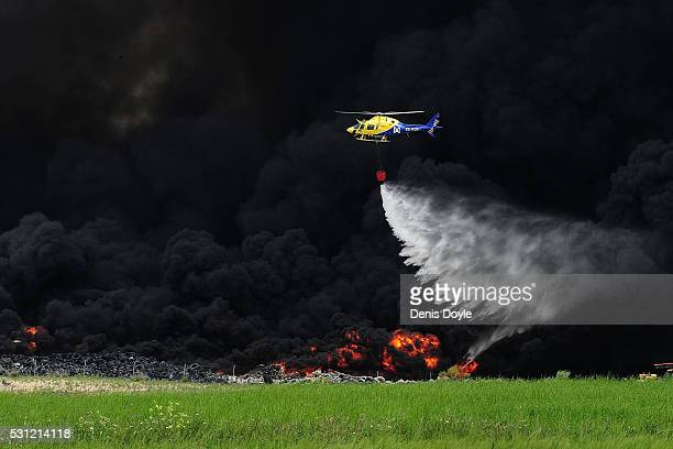 A helicopter drops water onto burning tyres at an illegal dump on May 13 2016 in Sesena Nuevo Spain The dump which stored over 75000 tonnes of used...